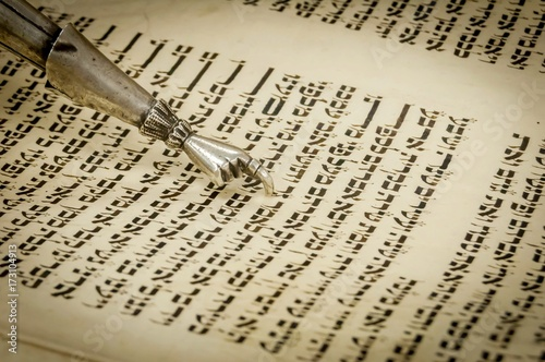 Fotografie, Obraz Torah pointer with a hand at the end with one finger extended to help read the text of holy scriptures of Torah