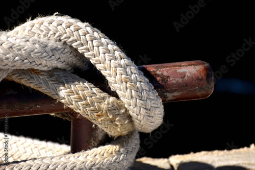 Rope knotted at a pier. With bollard.