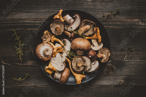 Fotografia Fresh mixed forest mushrooms on the wooden black table