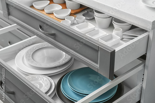 Set of tableware in kitchen drawers