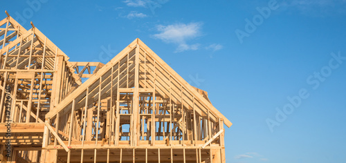 Photographie Close-up of gables roof on stick built home under construction and blue sky in Humble, Texas, USA