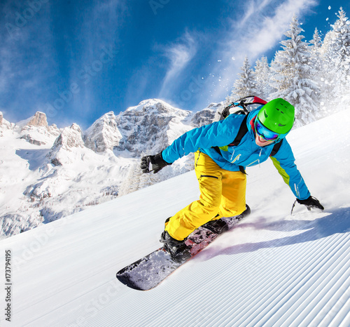 Snowboarder going downhill in high mountains