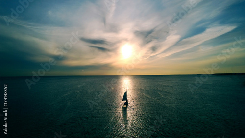 Tablou Canvas Little white boat floating on the water towards the horizon in the rays of the setting sun