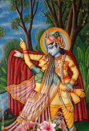 Wall art of Hindu god Sri Krishna and Radha playful in a garden in brindavan in a temple