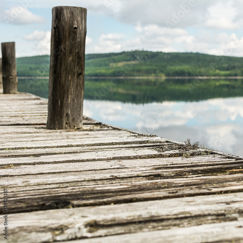 Old wooden pier on calm lake with reflection of mountains and cloudy sky. Dalarna region, Sweden