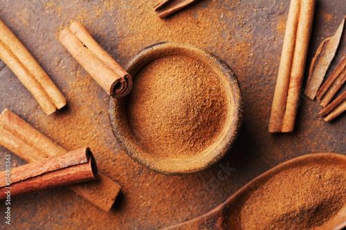 Fotografia Cinnamon sticks and powder on brown rustic table top view