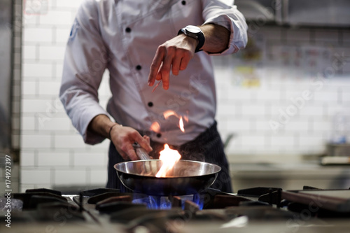 A man cooks cooking deep fryers in a kitchen fire.