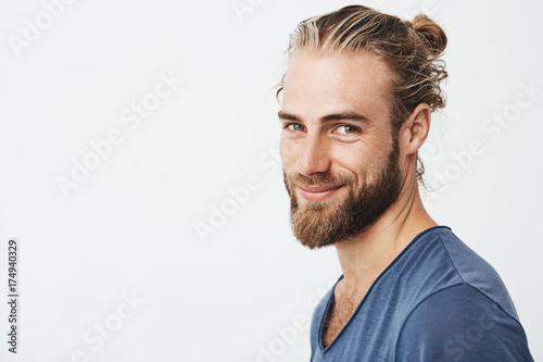 Carta da parati Close up portrait of handsome manly guy with beard posing in three quarters, looking in camera and happily smiling