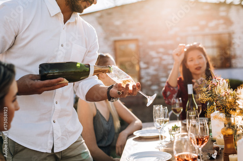 Photo Man serving champagne to friends during party