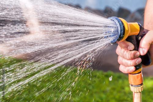 Obraz na płótnie watering the grass with hose