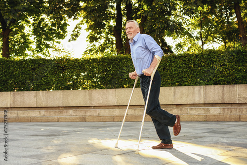 The old man on crutches strolls through the park. He is focused Fototapeta