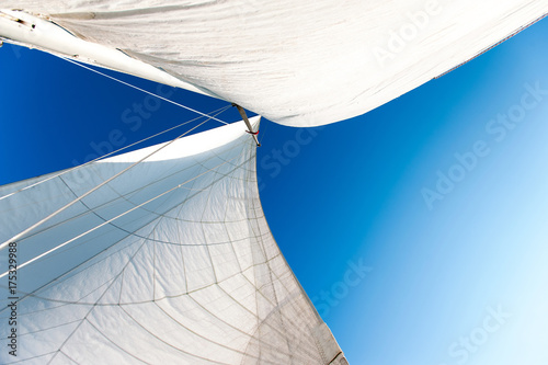 White yacht sails in sunlight on blue cloudy sky background.