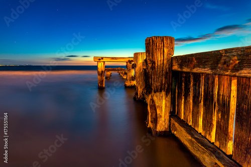 Wodden pier a dusk on a very calm day at the beach in Australia. The sky is blue and the atrmosphere is warm.