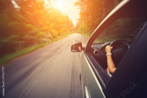Carta da parati Young beautiful woman driving car - rear view