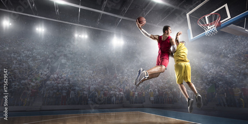 Basketball player makes slam dunk on big professional arena. Player flies through the air with the ball. Opponents try to prevent the ball from hitting the basketball ring.
