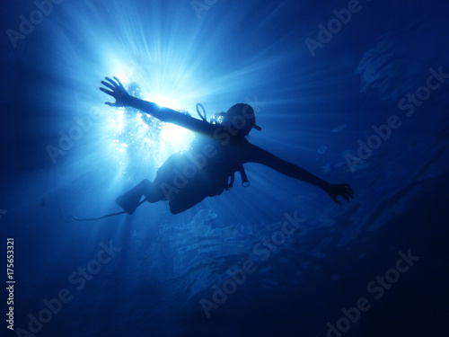 Person Swimming Underwater with Sun Rays Behind Fototapet
