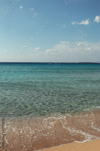 Greek beach with turquoise water and someone doing windsurf in the distance
