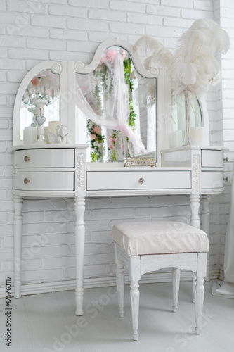 Valokuvatapetti White boudoir table with mirror, casket, candles and feathers on it near brick wall in white room, free space