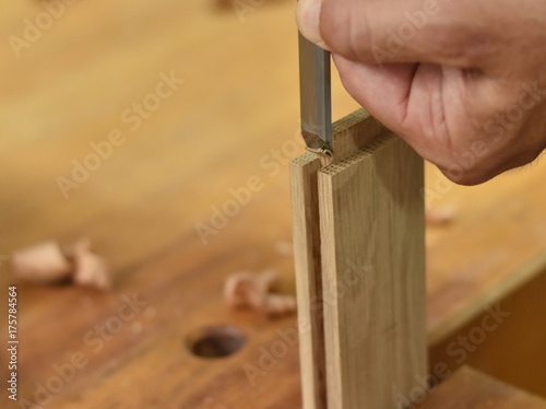 Obraz na plátne Woodworker removing wood shavings on white oak tenon joinery with a Paring Chise