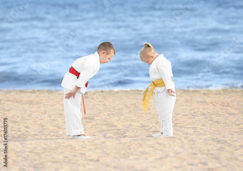Little children performing ritual bow prior to practicing karate outdoors