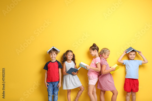 Cute little children with books on color background