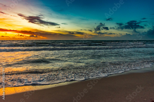 sunrise colored sky reflecting off the ocean on an early morning at the beach