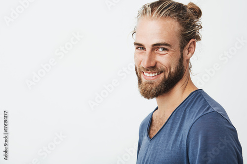Fototapeta Happy young bearded guy with fashionable hairstyle and beard looking at camera, brightfully smiling with teeth, being happy about day off on work