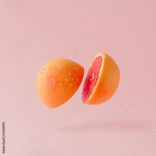 Grejpfruty w plasterkach na pastelowym różowym tle. Minimalna koncepcja owoców.