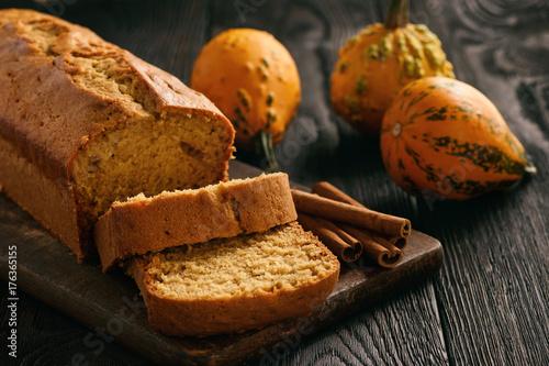 Homemade pumpkin cake on black wooden background.