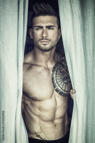 Photo Portrait of sexy shirtless muscular man next to window curtains during the day,