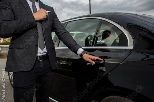Carta da parati Man opening a car limousine door