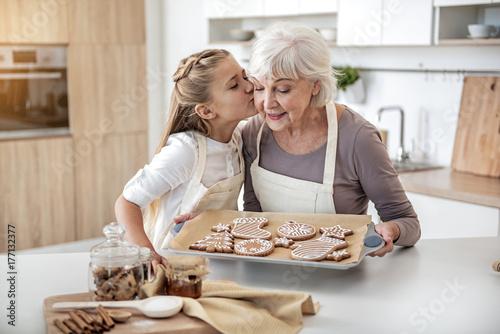 Fototapeta Happy child thanking grandma for sweet pastry