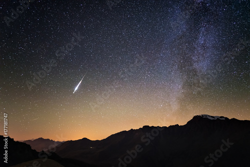 Milky Way and starry sky from high up on the Alps. Real Christmas comet in the sky. Majestic high mountain range with glacier and snow.