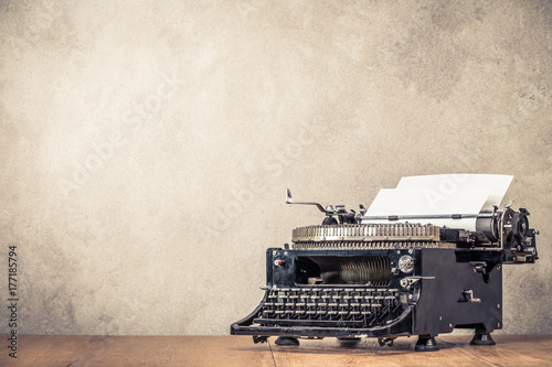 Vintage old aged black typewriter circa 40s with paper blank on wooden table front concrete wall background. Retro instagram style filtered photo