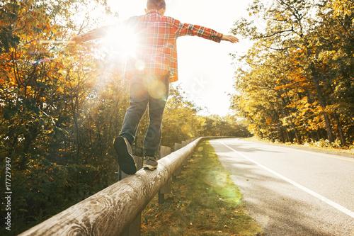 Fotografija boy walking along the road fence
