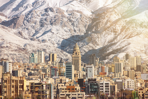 Winter Tehran  view with a snow covered Alborz Mountains on background. With lens flare and light leak