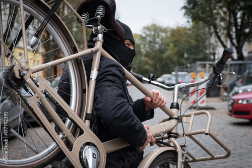 Photo Theft wearing a balaclava stealing a bicycle