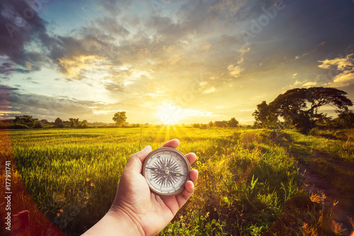 Canvas Print A man holding compass on hand at field and sunset for navigation guide