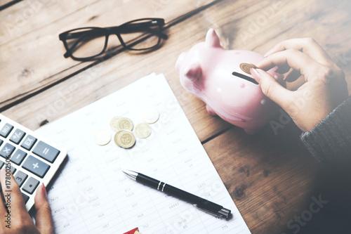Fotografija Female hand putting coin in piggy bank, on the office desk