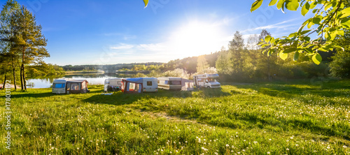 Foto Family travel concept. Caravans and camping on the lake.