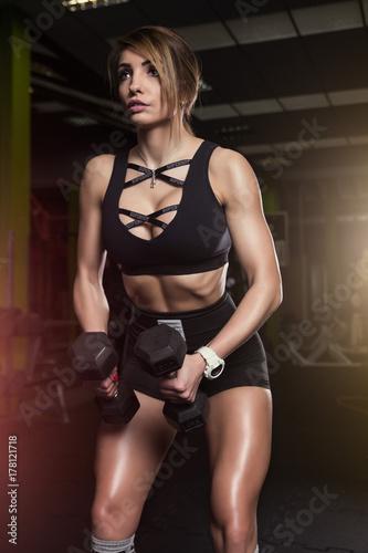 Fototapeta premium Dziewczyna na siłowni z hantlem