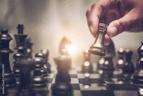 Tablou Canvas Businessman moving chess piece on chess board game concept for ideas and competition and strategy, business success concept, business competition planing teamwork strategic concept