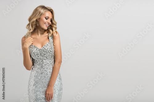 Fotografering Beautiful woman in shining silver dress on gray background.