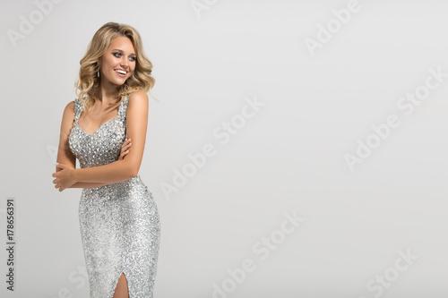 Valokuva Beautiful woman in shining silver dress on gray background.