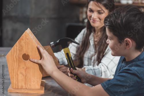 Slika na platnu Mother and son building birdhouse