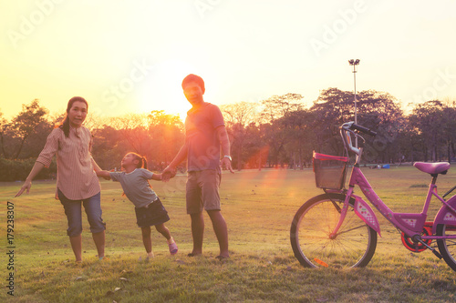 Family silhouette with bike, family on the front of the sunset.