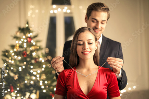 Fototapeta Handsome guy gifting a beautiful necklace to her girlfriend