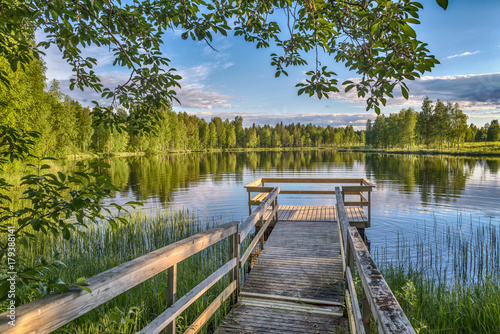 Canvas Print Pier with wooden benches at the lake in Lapland