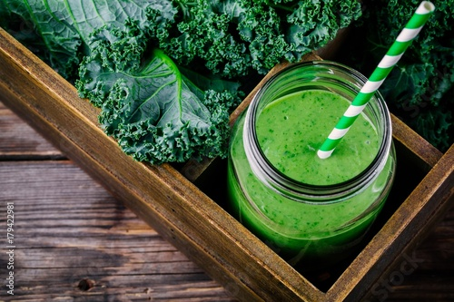 Healthy green smoothie with kale in mason jar on wooden background