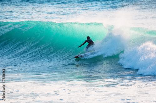 Surfer on blue wave. Winter surfing in ocean